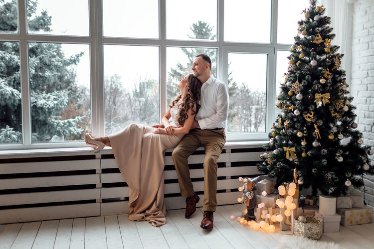 People sitting on christmas tree at home