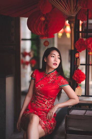 Beautiful Asian Chinese Woman Wearing Cheongsam Traditional Red Dress Siting on Chair Fashion Posting Chinese New Year Red One Person Real People Lifestyles Young Women Women Young Adult Three Quarter Length Clothing Leisure Activity Adult Indoors  Focus On Foreground Beautiful Woman Fashion Standing Front View Dress Hairstyle Cheongsam Chinese New Year Festival; Fashion Candid
