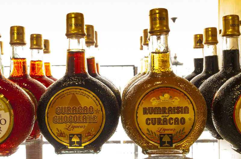 Curaçao is a liqueur flavored with the dried peel of the laraha citrus fruit, grown on the island of Curaçao. Communication Creativity Curacao Group Of Objects Laraha Citrus Fruit Liqueur Liqueur Bottle Man Made Object Non-western Script Retail  Text Western Script Willemstad