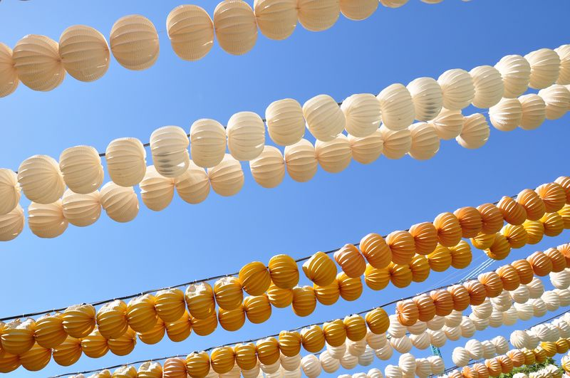 Low Angle View Of Multi Colored Lanterns Hanging Against Clear Blue Sky
