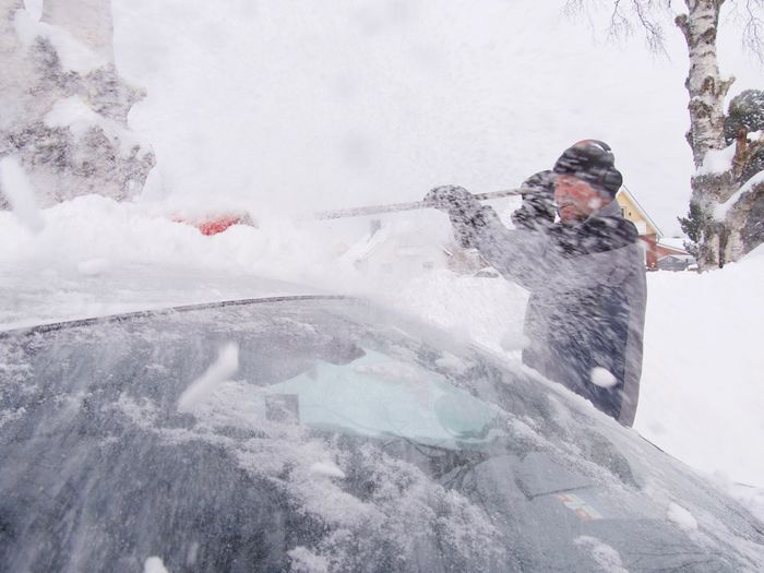 Senior man removing snow from car roof during winter