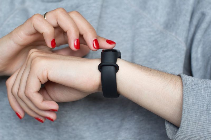 Young woman using smart watches Sportwear Sport Time Sports Equipment Time Wristwatch Sport Watch Monitor Touch Screen Scroll Social Issues Messaging Smart Watch Technology Human Hand Nail Polish Hand Nail Women Red Red Nail Polish Lifestyles Fashion Manicure