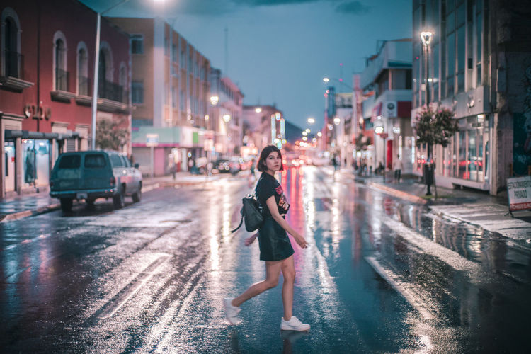 Wet city Architecture Building Exterior Built Structure City City Life City Street Full Length Illuminated Lifestyles Looking At Camera Night One Person Rain Real People Road Street Transportation Walking Wet Young Adult 2018 In One Photograph Moments Of Happiness