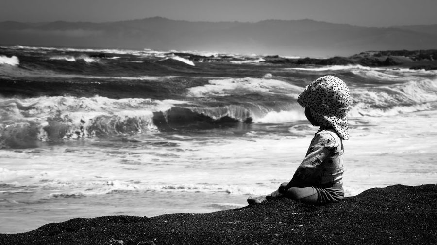 Girl With Cap Sitting At Beach Against Sky
