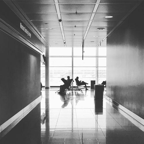 People sitting on chair seen through corridor