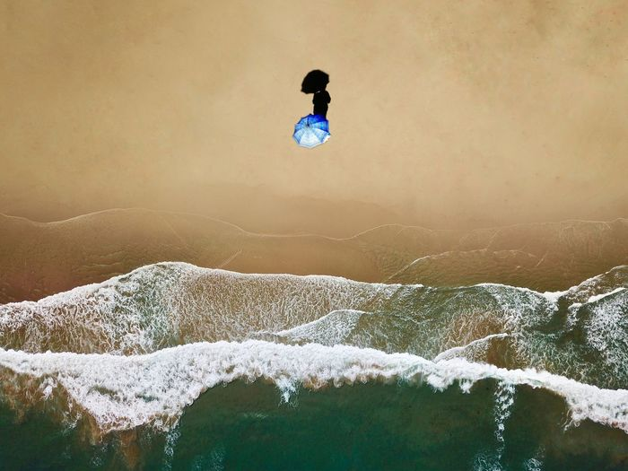 An aerial view of a woman at the beach holding umbrella Summer Views Shade Shadow Room For Text negative space Copy Space Minimal Drone Shot Drone  High Angle View Beach Aerial Beach Wave Waves Aerial Photography Umbrella Aerial Shot Aerial Aerial View One Person Motion Full Length Nature Digital Composite Leisure Activity Lifestyles Real People Adventure Water Adult Vitality