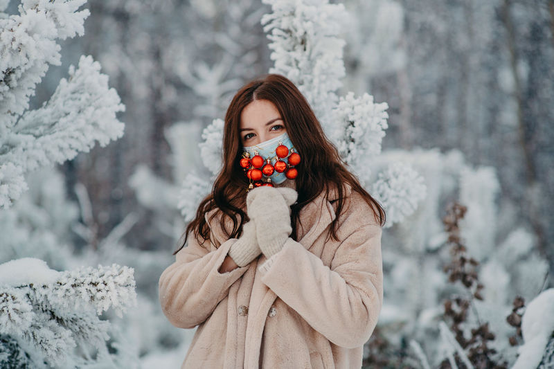 Woman standing by snow covered plants during winter