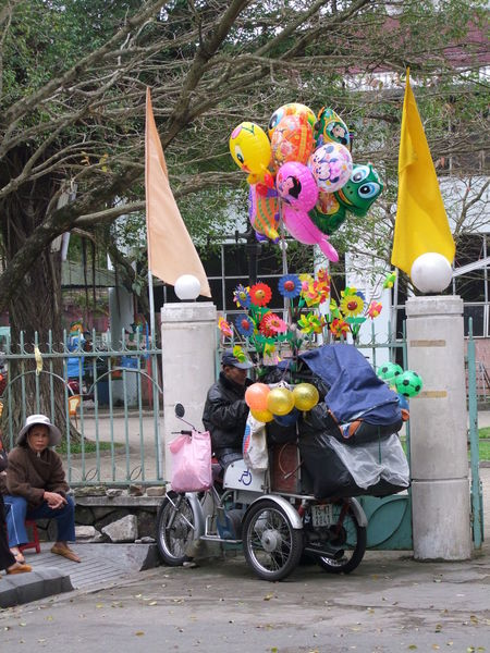 Street Vendor Balloons Colourful Composition Cyclo Day Flags Flowers Full Frame Huế Leisure Activity Lifestyles Making A Living Mode Of Transport No Incidental People Outdoor Photography Outdoors Retail  Selling Street Street Vendor Sunlight Transportation Trees Vietnam Woman