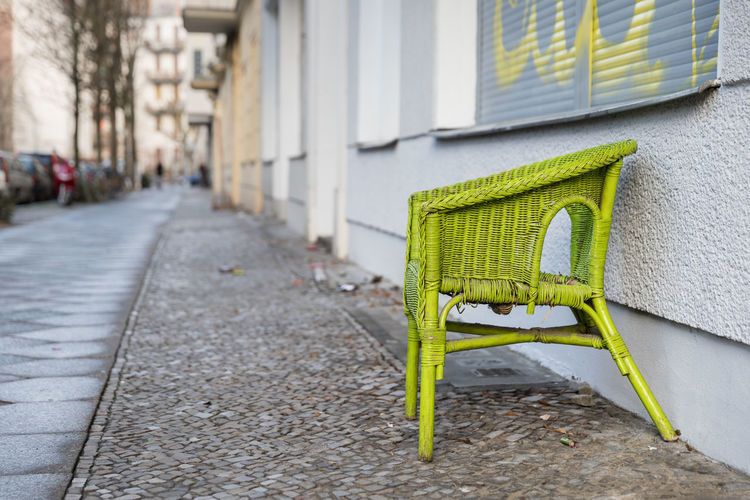 Green Wicker Chair On Footpath By Building