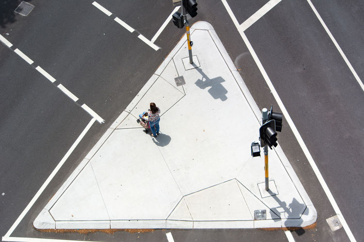 Street markings as seen from above. One person waiting to cross street. Aerial View Day From Above  Gray Color Grey Color High Angle View One Person Outdoors People Road Marking Road Markings Street Marking Street Markings Triangle Triangle Shape White Color The City Light Flying High The Street Photographer - 2017 EyeEm Awards