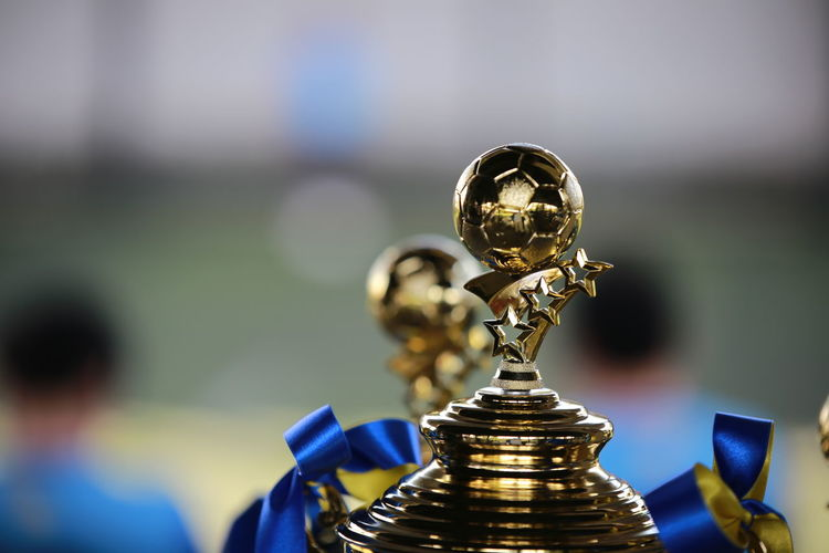 Close-up of golden football shaped trophy against blurred background