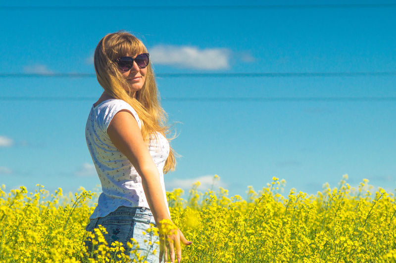 Low angle view of young woman against yellow flowers on field