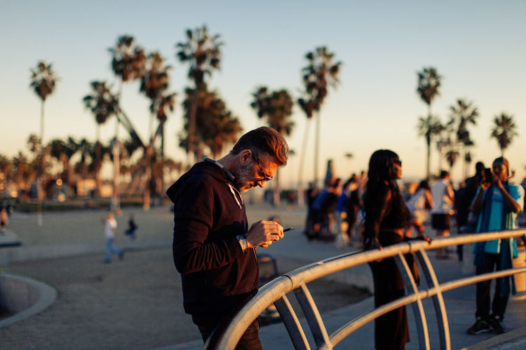 Adult man with beard looking at his phone during sunset at a skatepark with palm trees in background