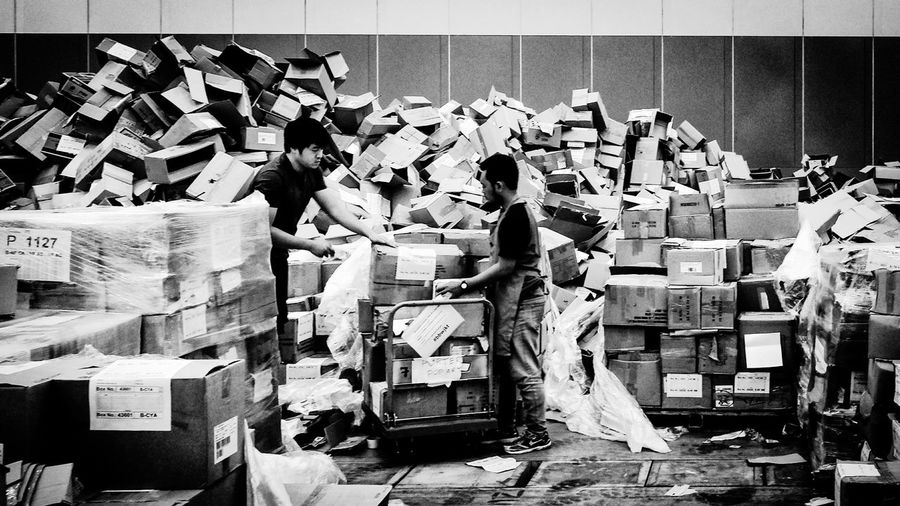 Men working with cardboard boxes at warehouse