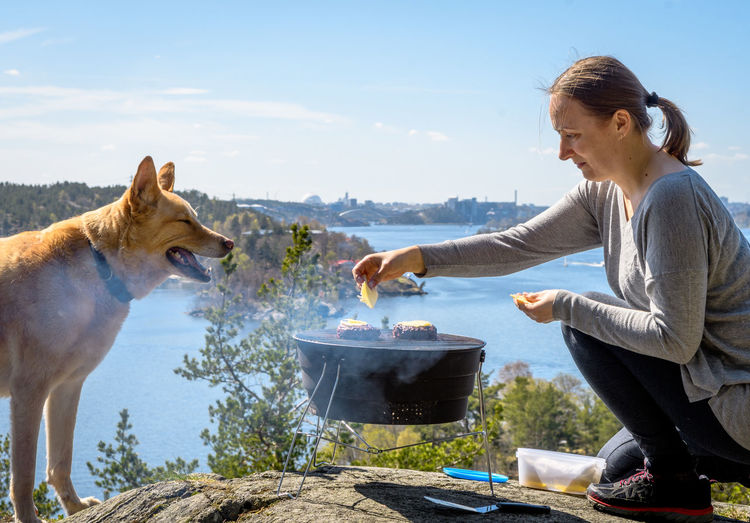 Side View Of Woman Preparing Food By Dog On Cliff