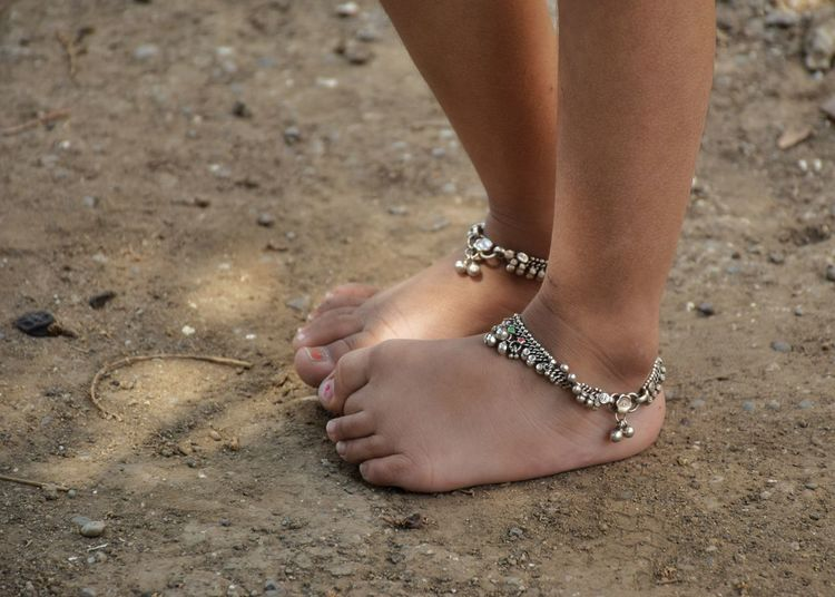 Low section of woman wearing anklet