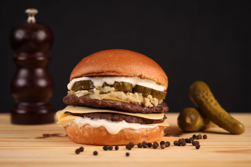 Close-up of burger on table against black background