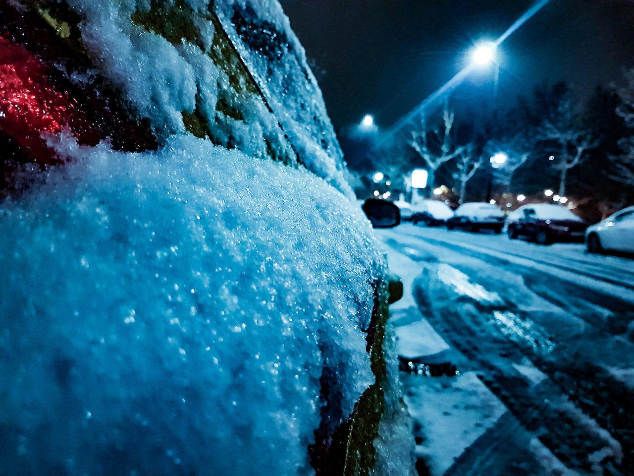 CLOSE-UP OF SNOW ON ILLUMINATED ROAD AT NIGHT
