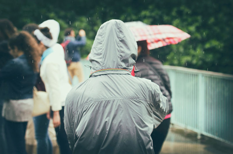 Rear view of person wearing raincoat while standing outdoors during rainfall