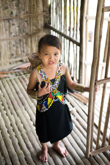 Portrait of cute girl standing on wooden floor