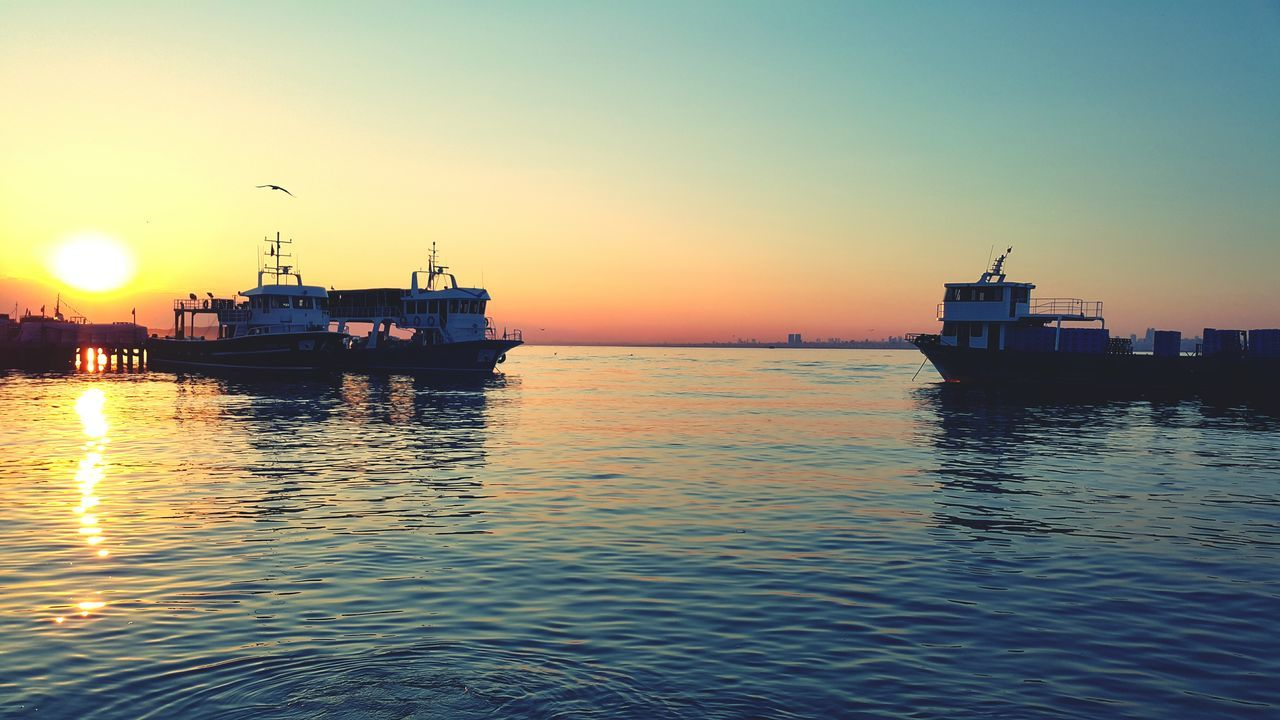Boats Sailing In Sea Against Clear Sky During Sunset
