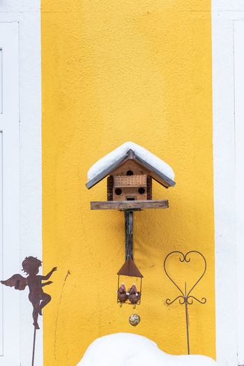 Homemade wooden bird's feeder in winter, under snow. yellow and white wall as a background.