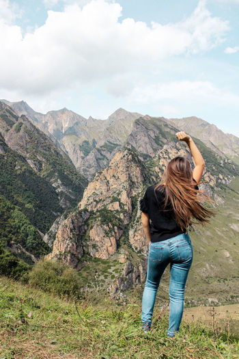 Rear View Of Woman With Hand Raised Standing Against Mountains