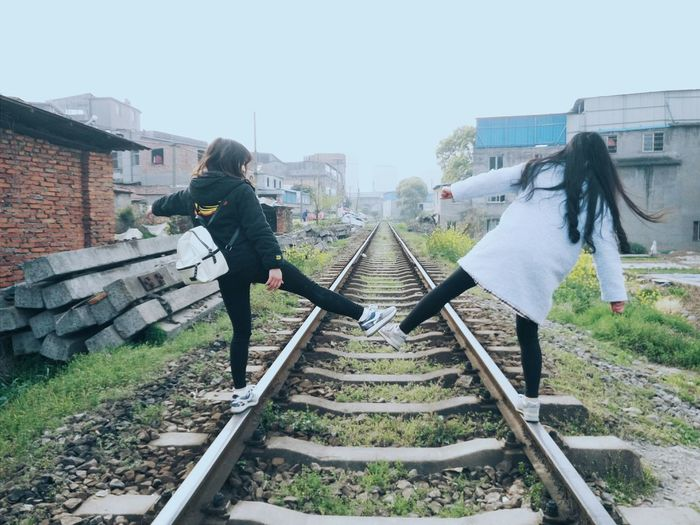 Full Length Rear View Of Friends Balancing On Railroad Track Against Sky
