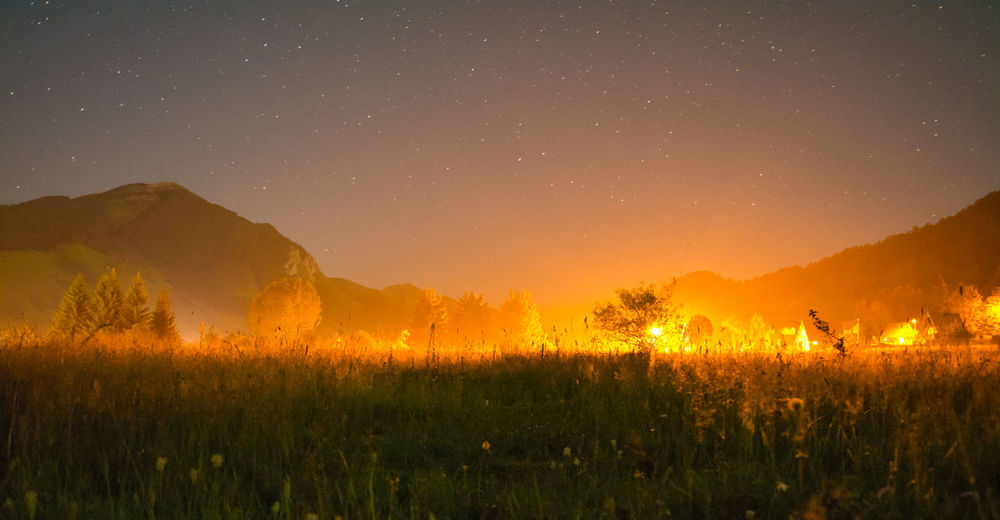 Illuminated Landscape With Sky In Background