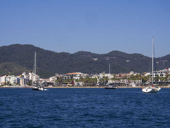 Yachts sailing on aegean sea against clear blue sky