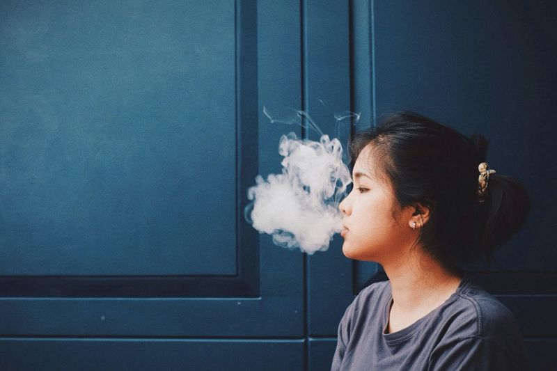 Woman Smoking Against Door