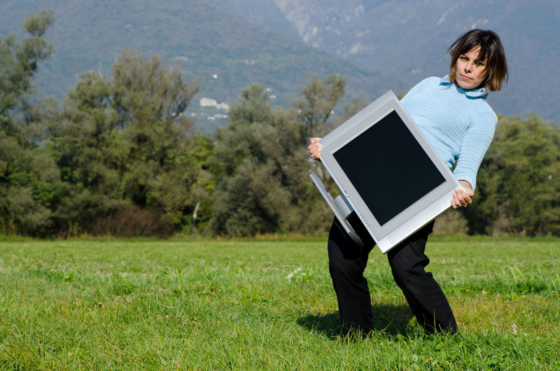 Portrait Of Woman Carrying Heavy Television Set On Grassy Field