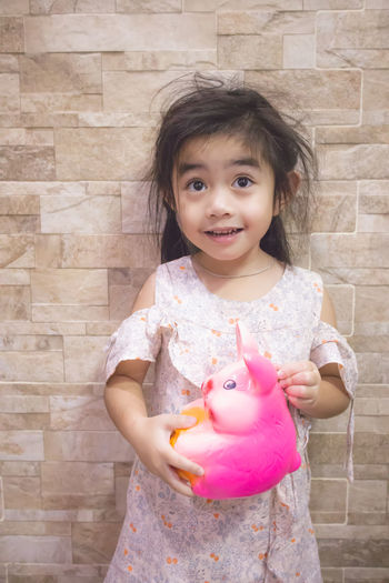 Portrait of cute girl holding pink face against wall