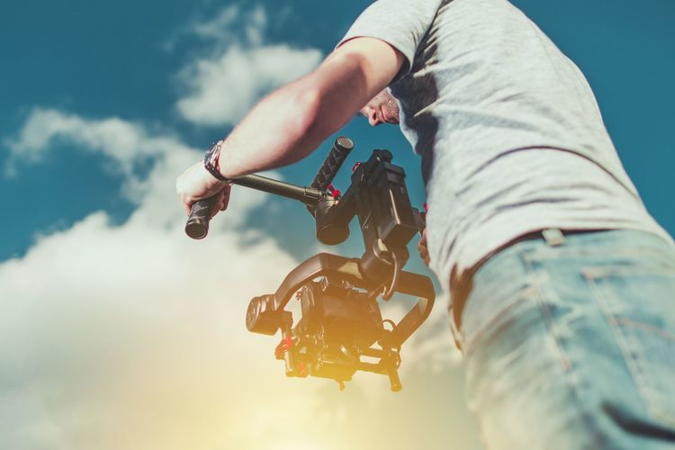 Men Taking Video Shots Using DSLR Camera and the Gimbal For Stabilization. Adventure Bicycle Close-up Day Gimbal Human Hand Low Angle View Men Motion Picture One Person Outdoors People Sky Video Producing Videomaker
