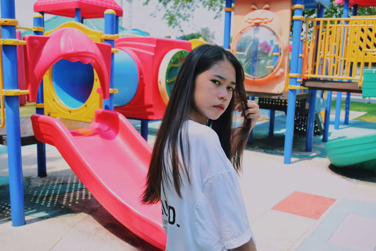 Portrait Of Teenage Girl Standing Against Play Equipment At Park