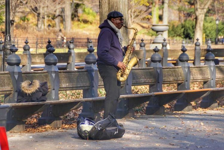 Side view of man playing trumpet while standing on road