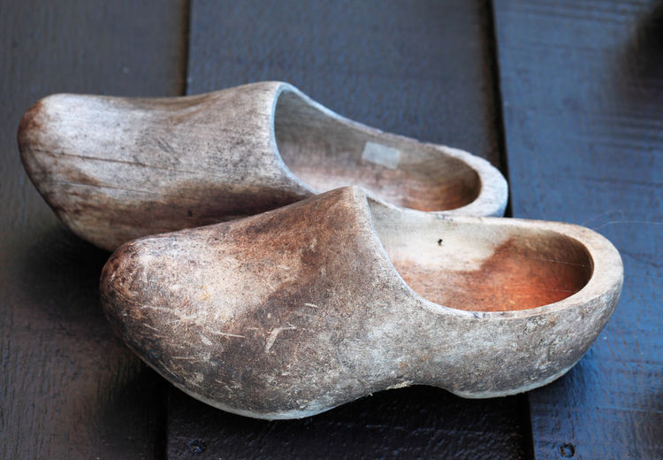 Old used traditional dutch wooden clogs on a wooden surface. Wood - Material Close-up No People Still Life Old Craft Focus On Foreground Art And Craft Simplicity Shoes Clogs Wooden Clogs Dutch Clogs Dutch Wooden Clogs