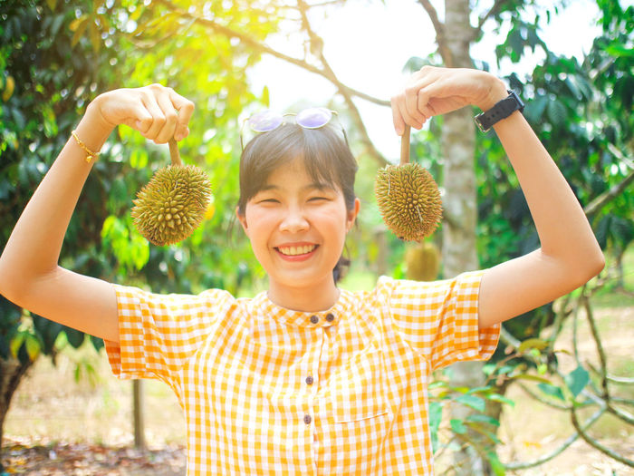 Portrait of smiling young woman holding durians at farm