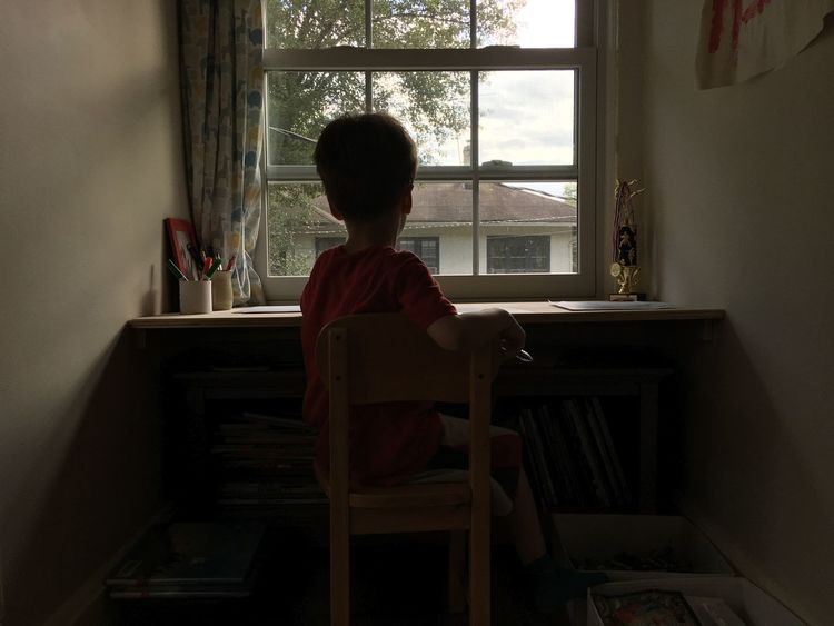 Boy Casual Clothing Contemplation Day Domestic Room Drawing Full Length Home Homework Kid Leaning Leisure Activity Lifestyles Looking Out Of The Window Playing Sitting Sitting On Table Sitting On Window Table Window Writing