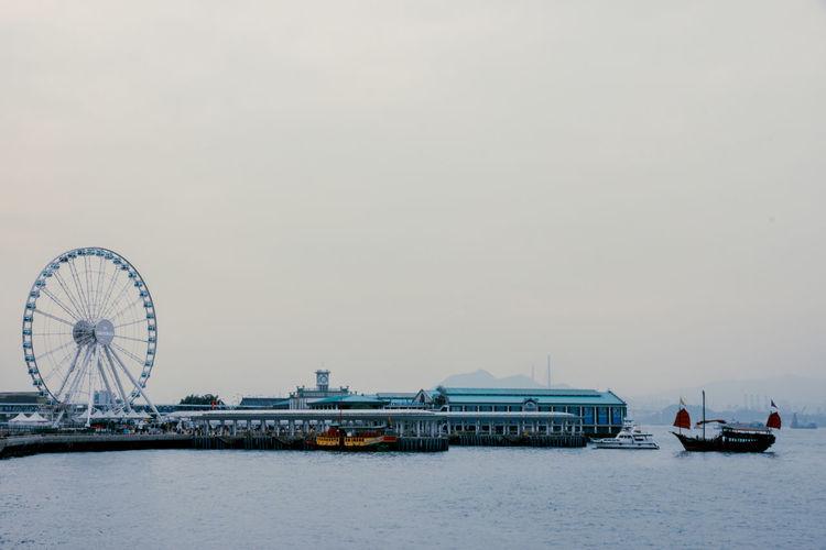 Hong kong observation wheel at victoria harbor against sky