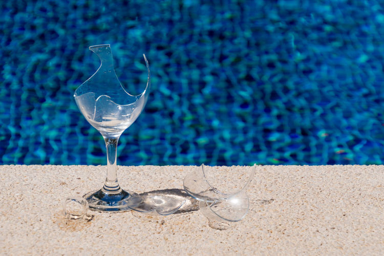 High Angle View Of Broken Wineglass At Poolside