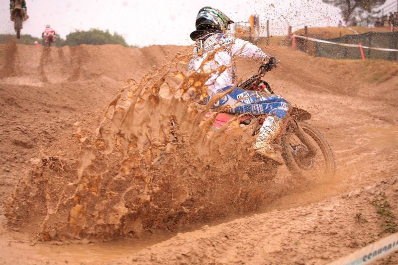 Man riding dirt bike on muddy track