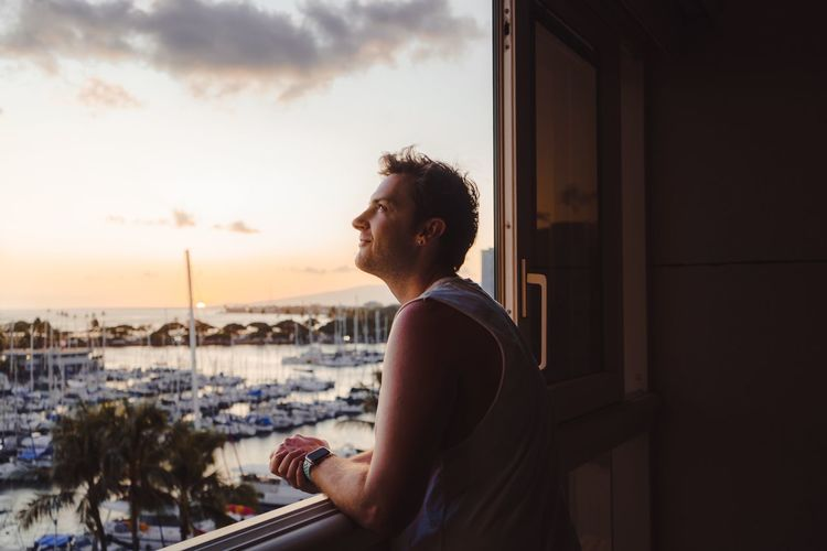 Man looking through window during sunset