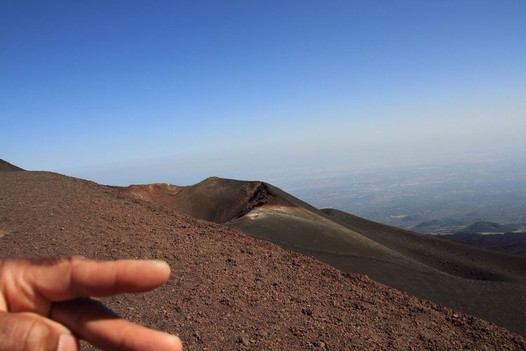 Cropped hand of person at mount etna against sky