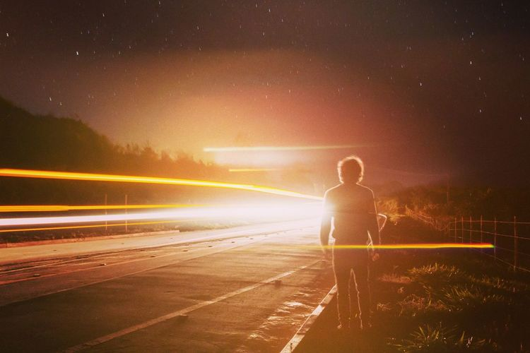 Rear view full length of man standing by light trails at roadside during night
