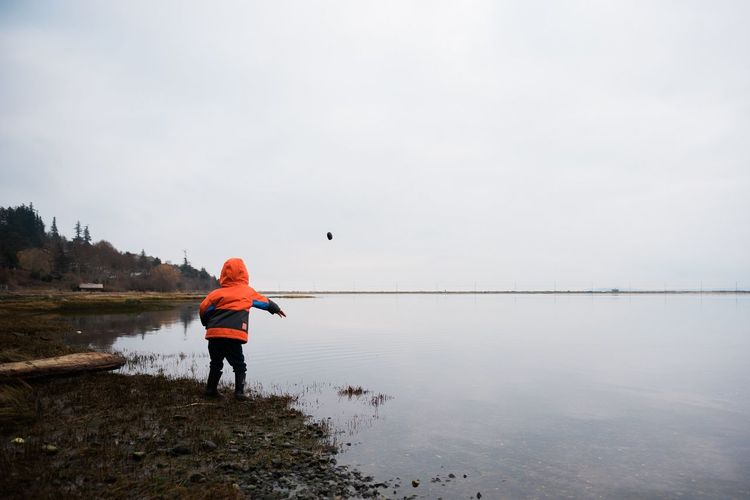 Rear view of child throwing stone in lake against sky