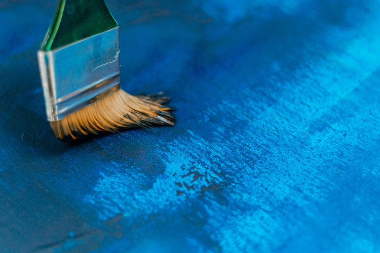 Close-up of paintbrushes on blue table