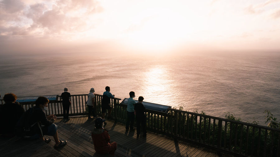 People sitting on railing by sea against sky during sunset