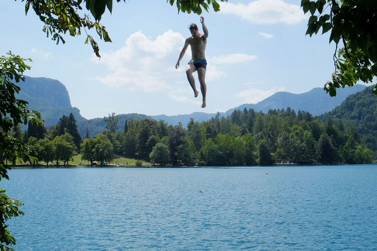 Man jumping over lake against sky