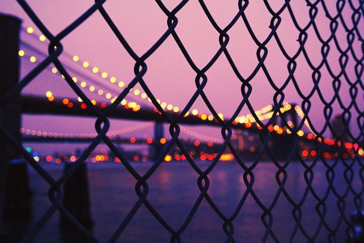 Illuminated bridge over river seen through silhouette chainlink fence against clear sky during sunset